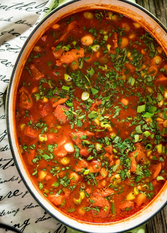 overhead of a large pot filled with mexican pork stew and garnished with parsley and green onion