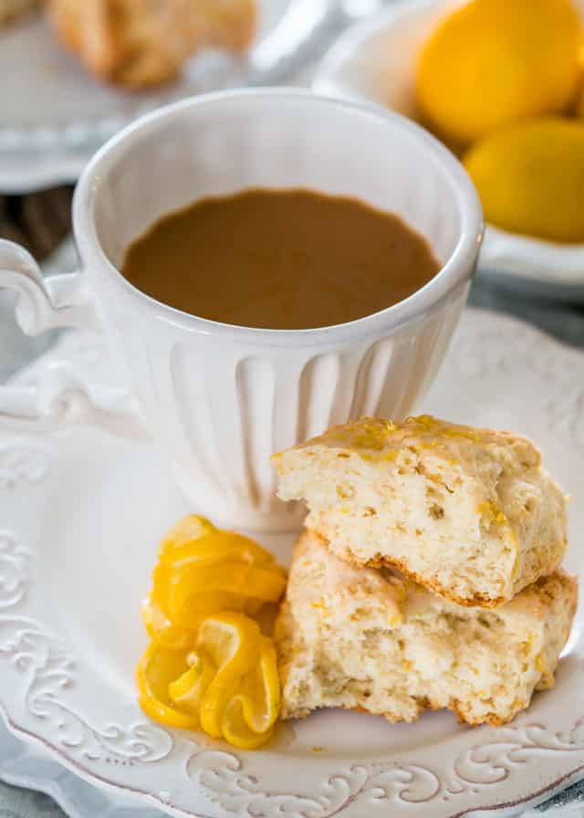 a scone split in half on a plate with a cup of coffee and lemon slices