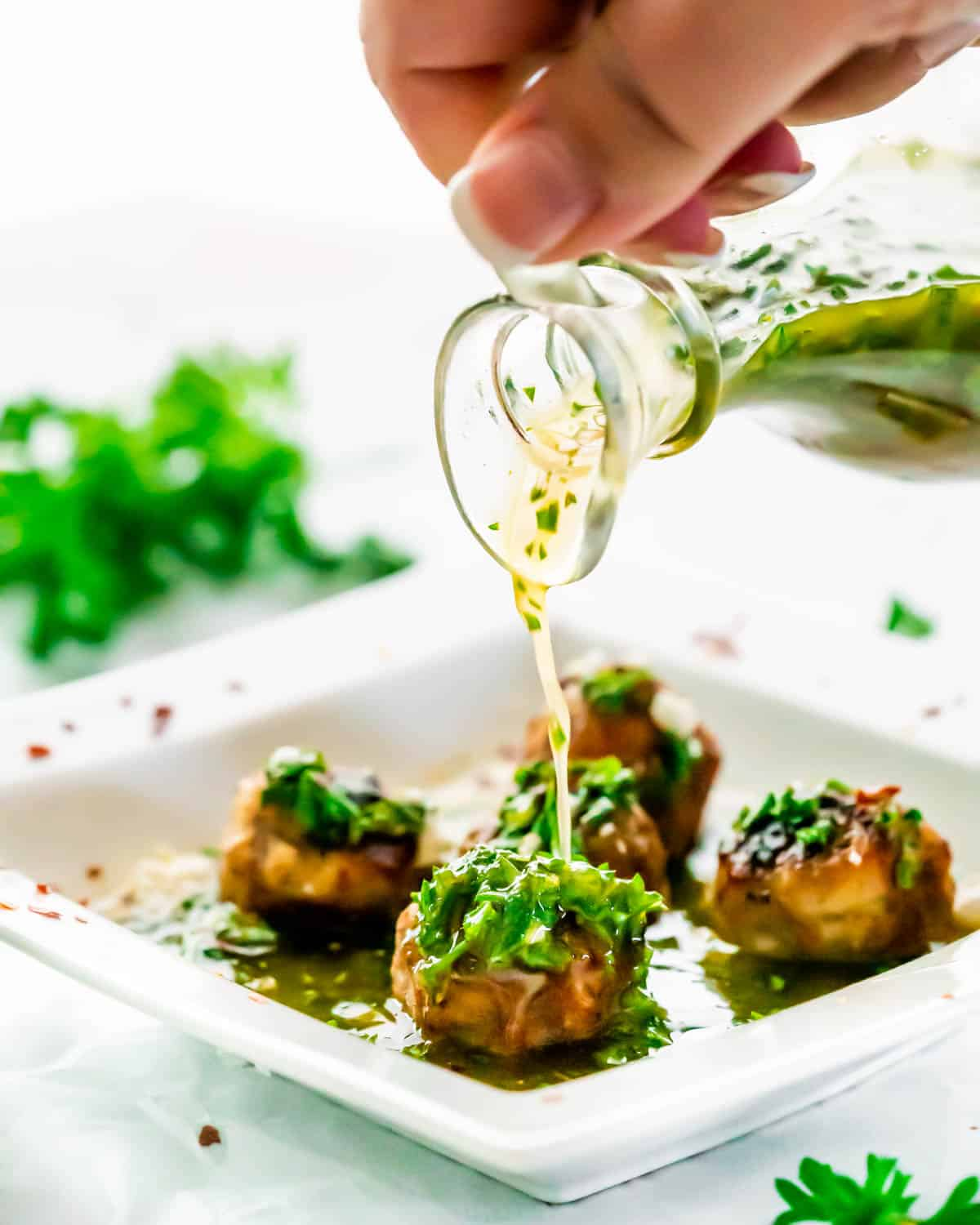 pouring chimichurri sauce over meatballs