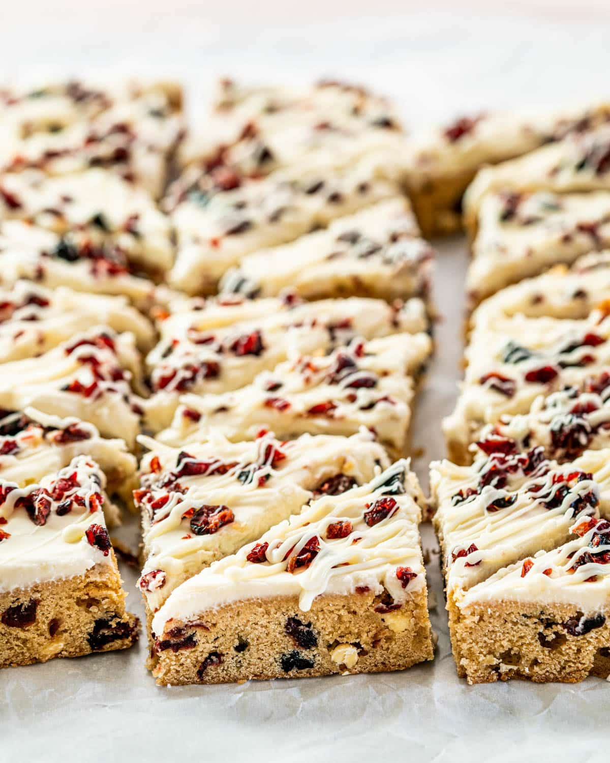cranberry bliss bars on parchment paper cut into triangles