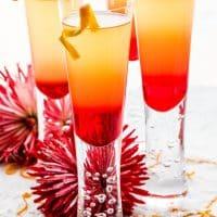 close up shot of 4 grenadine sunrises garnished with orange twists