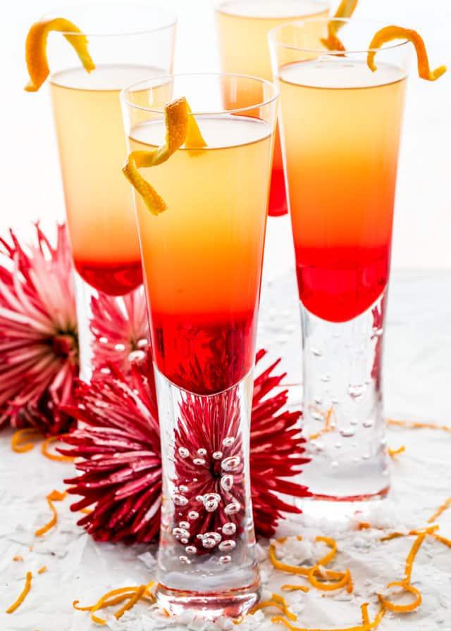 four glasses of grenadine sunrise with twists of orange
