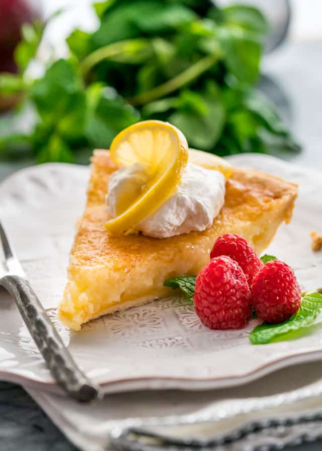 a slice of lemon pie on a white plate with a dollop of whipped cream, a slice of lemon, 3 raspberries, and a fork