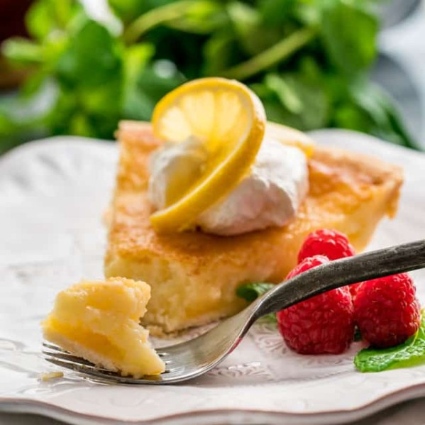 side view shot of a fork taking a bite of a slice of lemon chess pie topped with whipped cream and a slice of lemon on a plate garnished with fresh raspberries