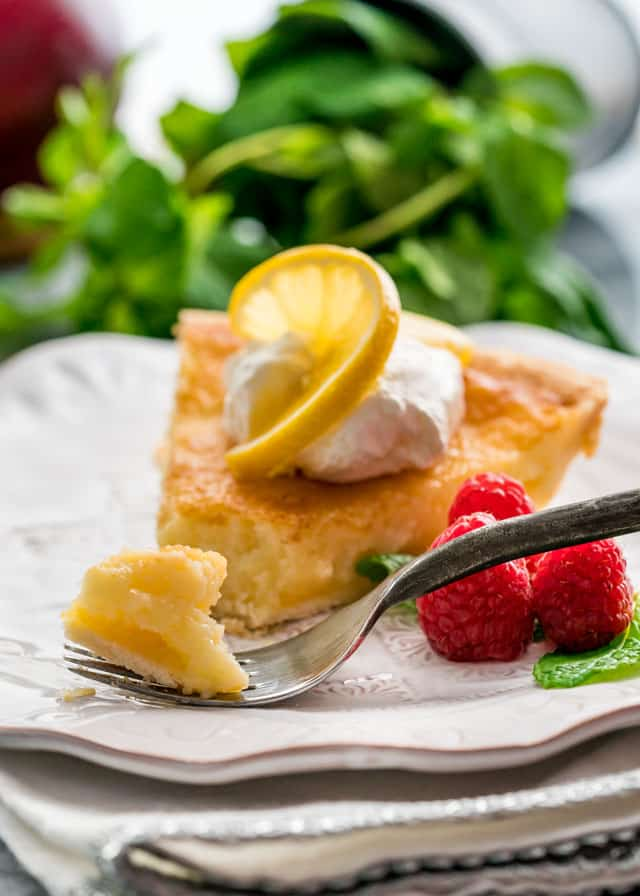 a piece of lemon pie on a plate with a few raspberries and a fork scooping a piece off