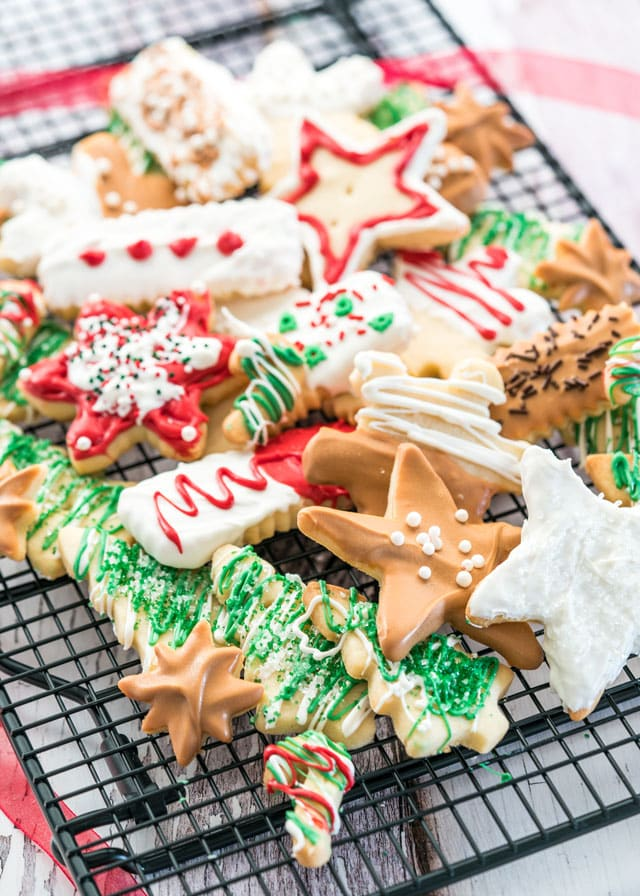 a pile of festively decorated shortbread cookies on a cooling rack