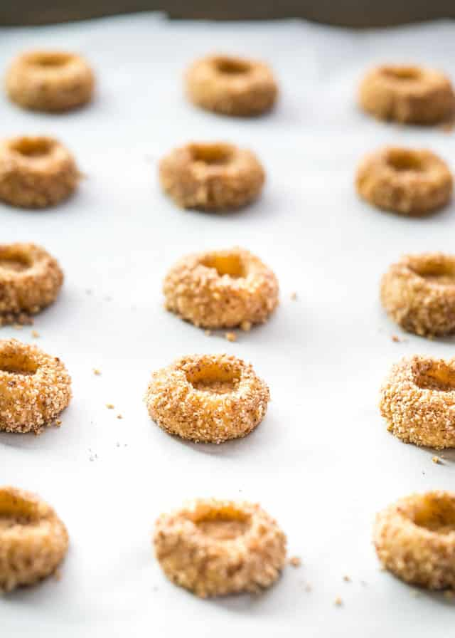 thumbprint cookies lined up on a baking sheet