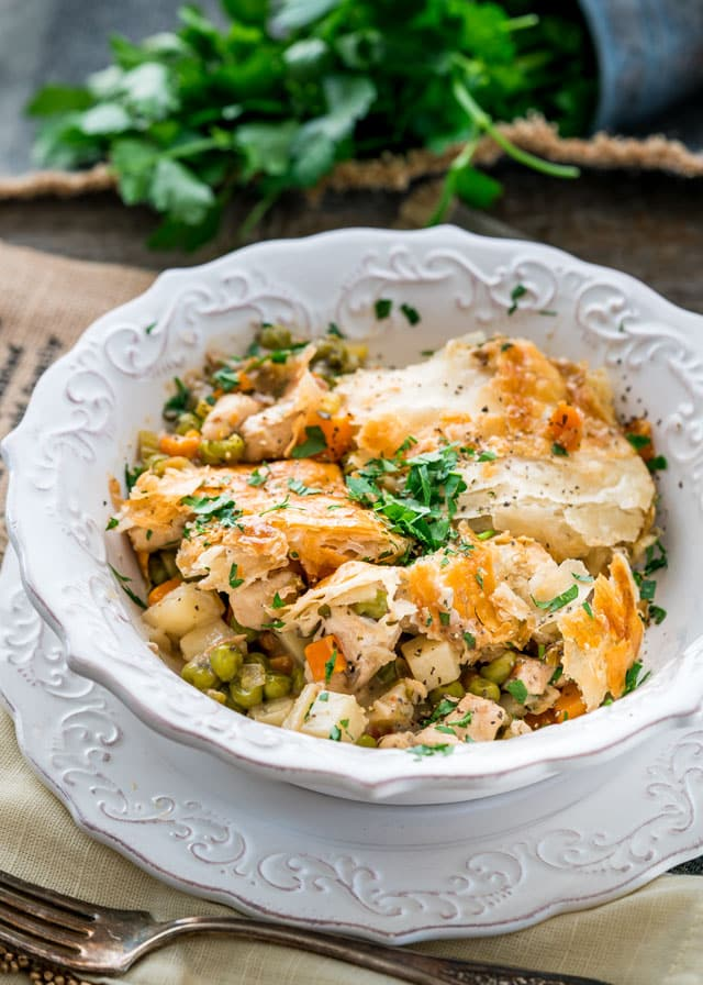 a bowl filled with chicken pot pie and flaky pastry