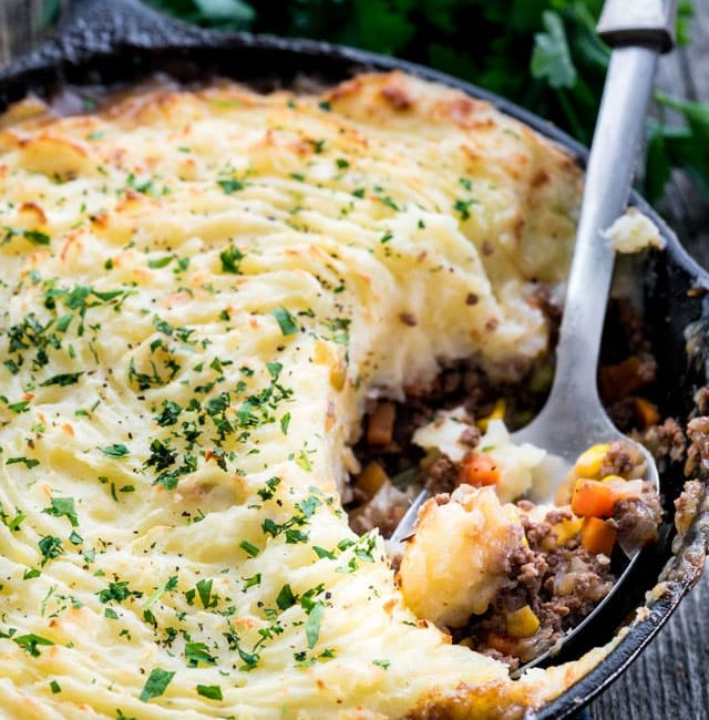 side view shot of a serving spoon taking a scoop of skillet shepherds pie