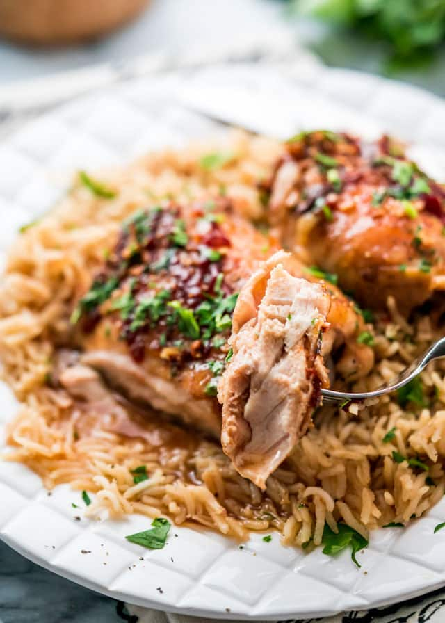 a fork holding a bite of chicken with a plate of chicken thighs and rice in the background