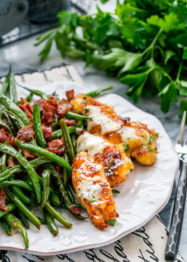 a plate of green beans with bacon and chicken