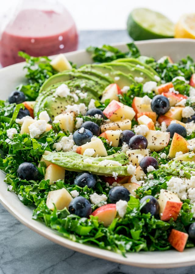 kale salad on a large platter with blueberry vinaigrette in the background
