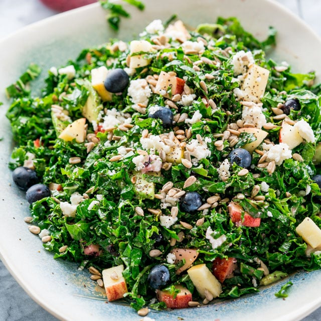 a bowl full of kale salad with blueberries, apple, sunflower seeds, and feta.