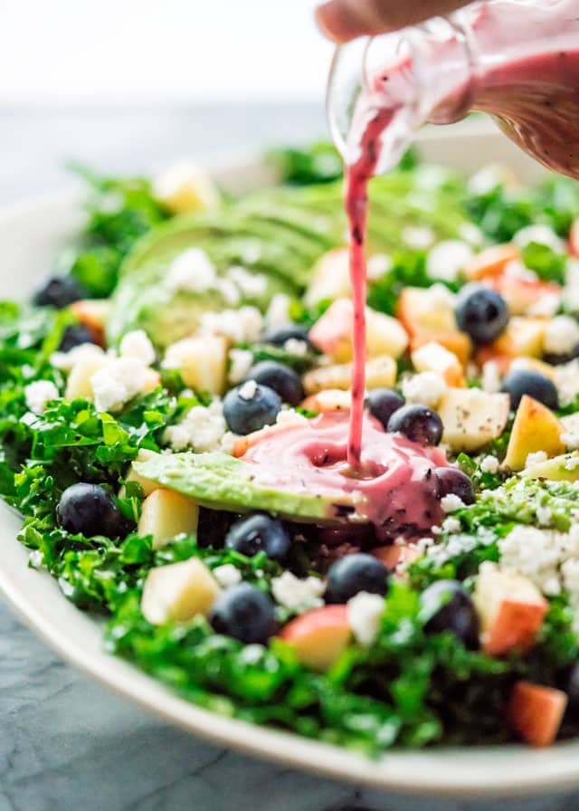 pouring dressing over a salad with kale, apples, and blueberries
