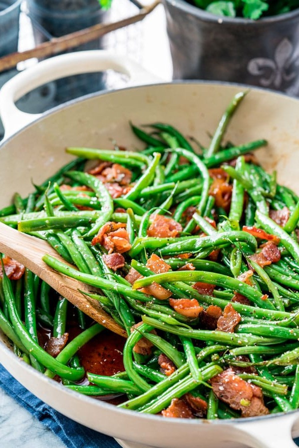 side view shot of green beans and bacon in a pan being stirred by a wooden spoon