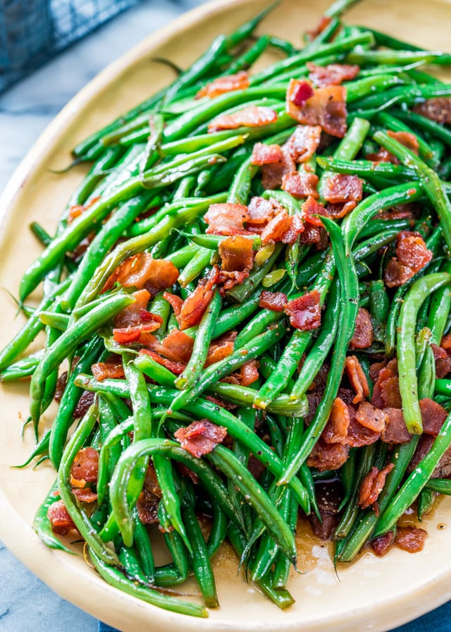 a platter of green beans covered in sauce and bacon