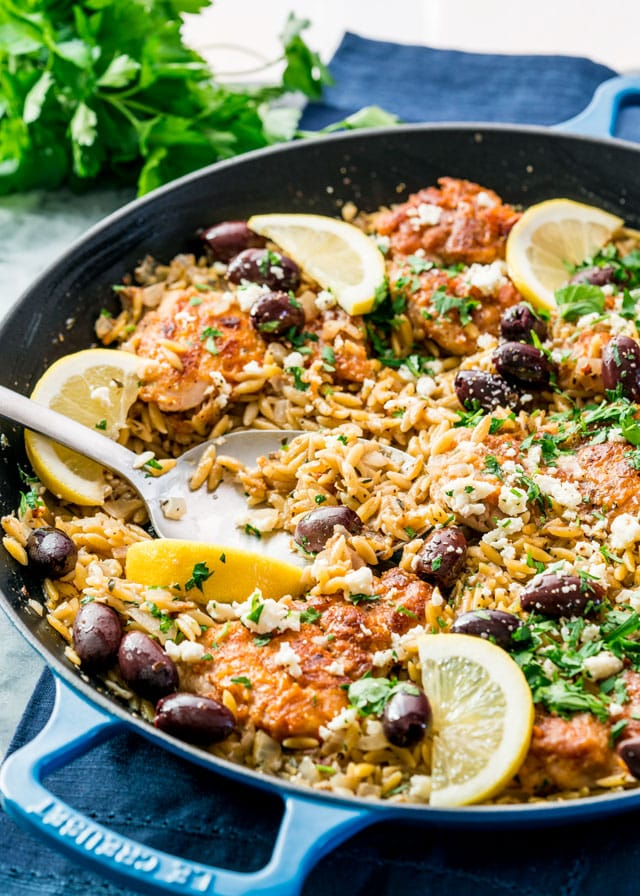 a braiser full of orzo with olives, chicken, and lemon slices.