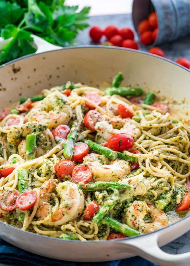 a braiser full of pasta with pesto, prawns, asparagus, and cherry tomatoes