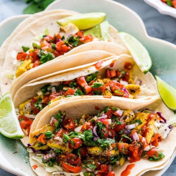 3 vietnamese fish tacos on a plate garnished with lime wedges