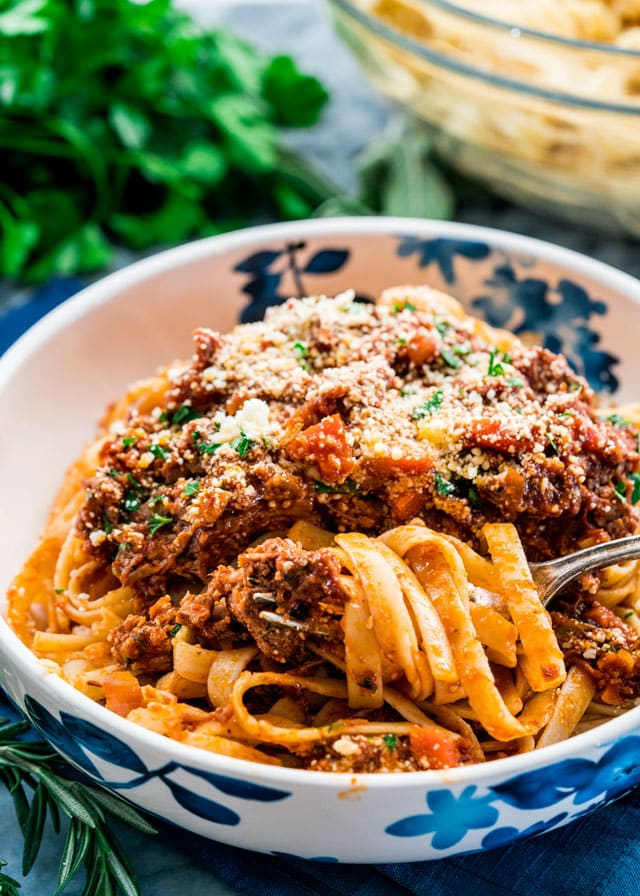 a bowl of ragu with fettuccini twirled around a fork