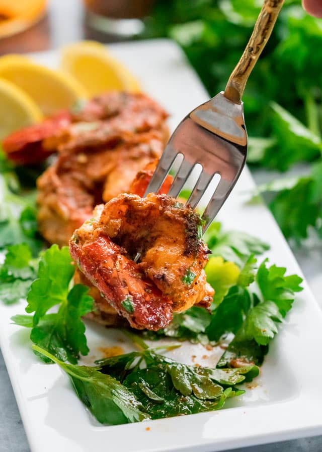 a prawn on a fork with a small plate of prawns, lemon wedges, and parsley in the background