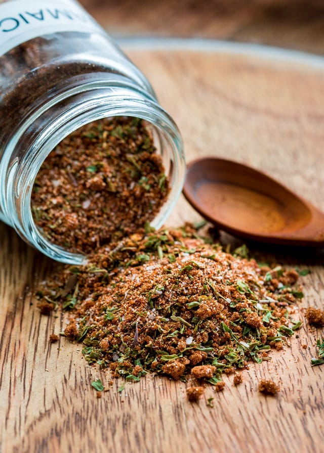 jerk spice blend spilling out of a glass jar with a small wooden spoon