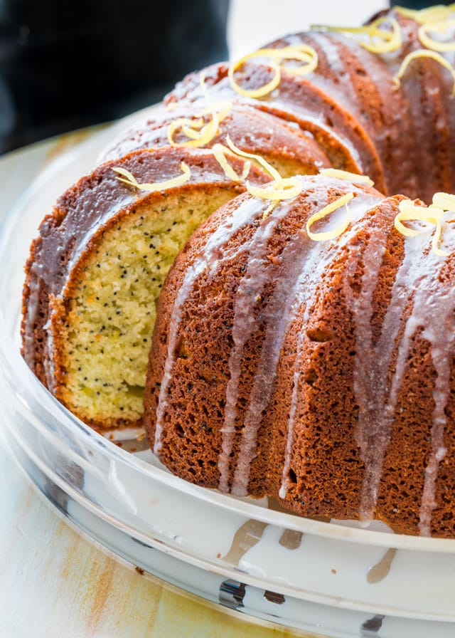 a lemon poppyseet bundt cake with a slice sticking out