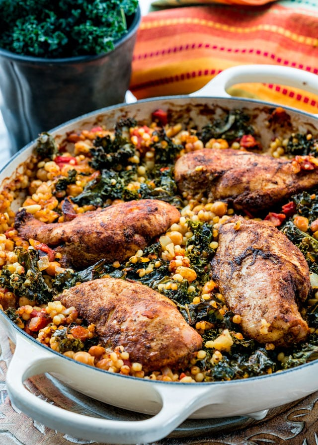 a braiser full of pearl couscous, kale, and spiced chicken breasts