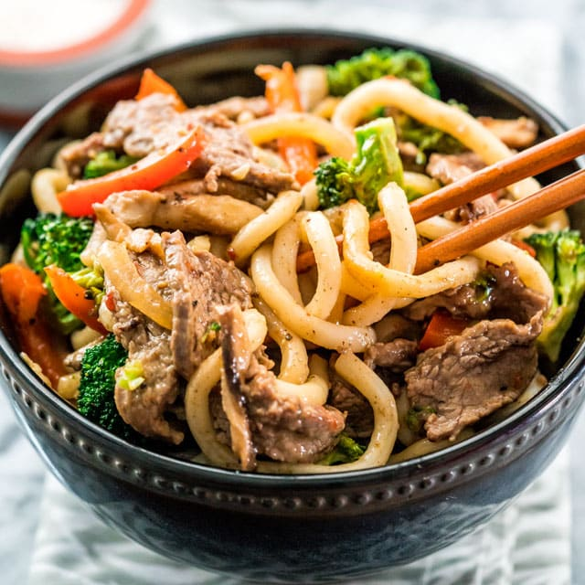 a bowl full of noodles with beef, broccoli, and red peppers