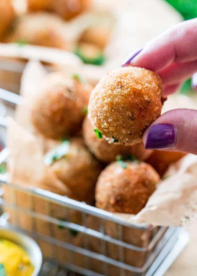 a hand holding a crispy dutch meatball