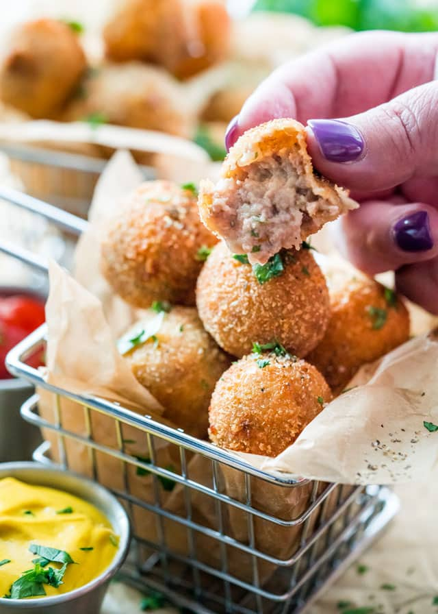 a hand holding a crispy dutch meatball with a bite taken out of it