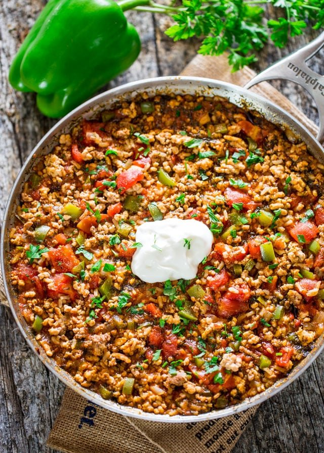 overhead of a pan filled with rice and vegetables topped with sour cream with a bell pepper