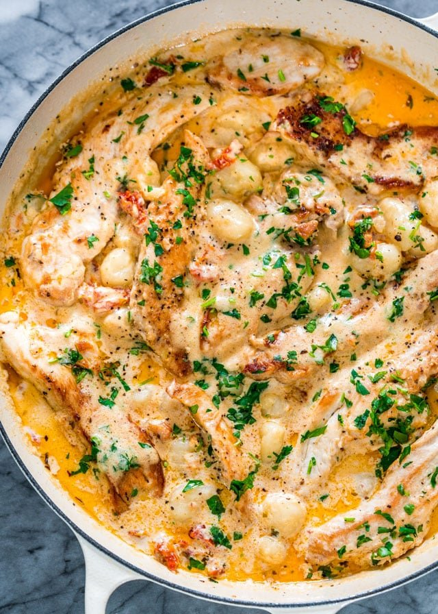 overhead of a braiser filled with gnocchi and chicken in a creamy sauce topped with parsley