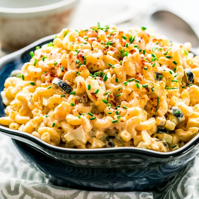 a large serving bowl full of macaroni salad topped with chives and paprika