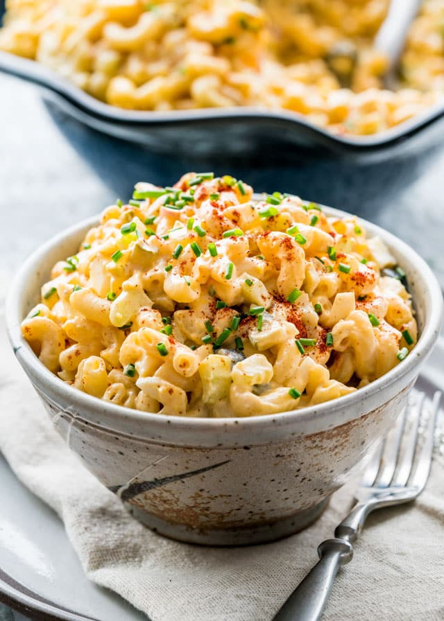 a bowl of macaroni salad topped with chives and paprika with a fork