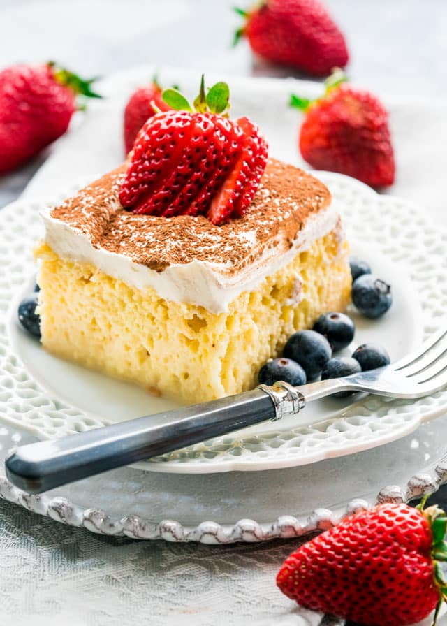 a plate with a slice of tres leche cake with strawberries and blueberries