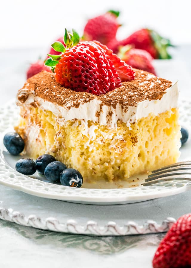 a piece of tres leche cake on a plate with blueberries and strawberries