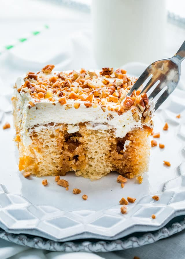 a poke cake topped with whipped cream, pecans, and toffee bits with a fork
