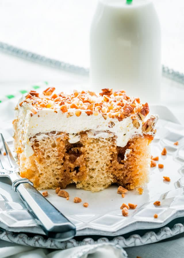 a slice of poke cake with whipped cream, pecans, and toffee bits with a fork
