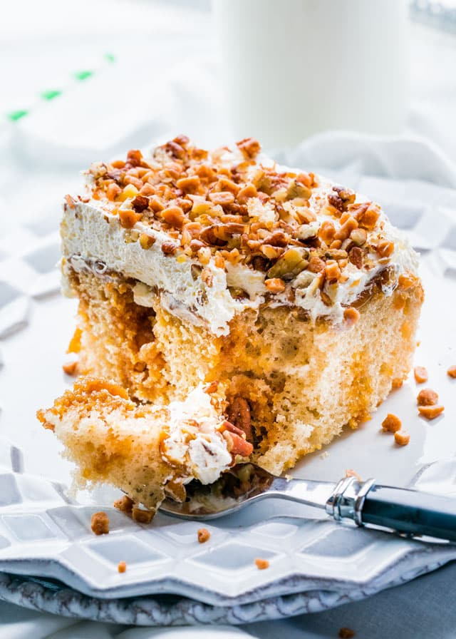 a plate with a piece of poke cake topped with whipped cream, pecans, and toffee bits
