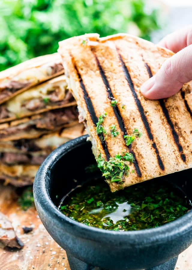 These Grilled Chimichurri Steak Quesadillas are just in time for your Memorial Day weekend party! Marinated steak in a yummy chimichurri sauce, Monterey Jack cheese and sautéed onions enclosed in a Flatout light flatbread, then grilled to perfection! This is how you make perfect quesadillas!