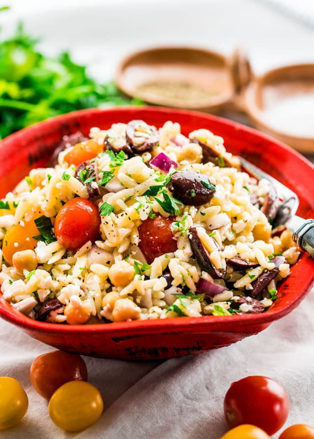 a bowl of orzo salad with a fork