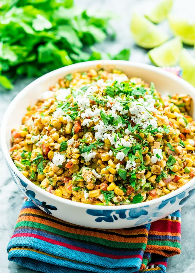 Mexican Street Corn Salad in a bowl topped with cotija cheese and parsley