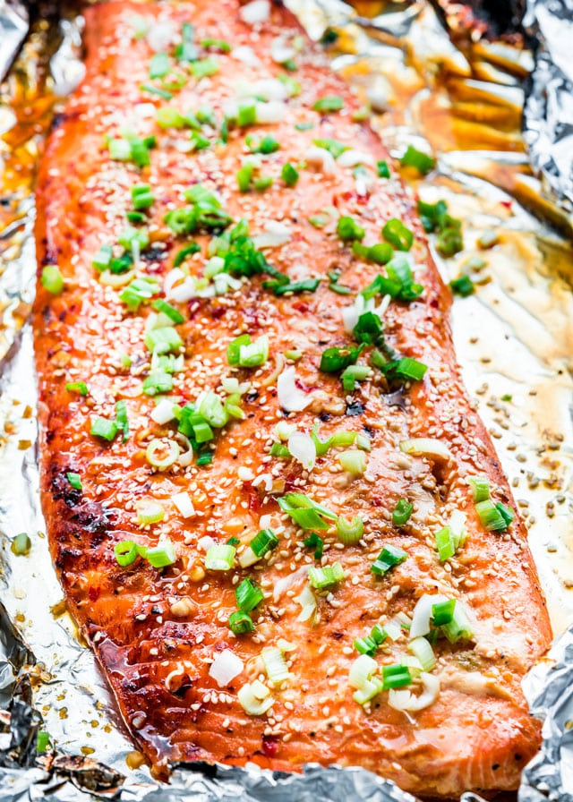 overhead of glazed salmon in foil topped with sesame seeds and green onion
