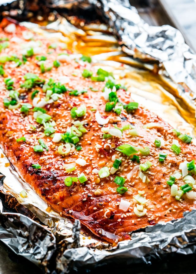 glazed salmon in foil topped with sesame seeds and green onion