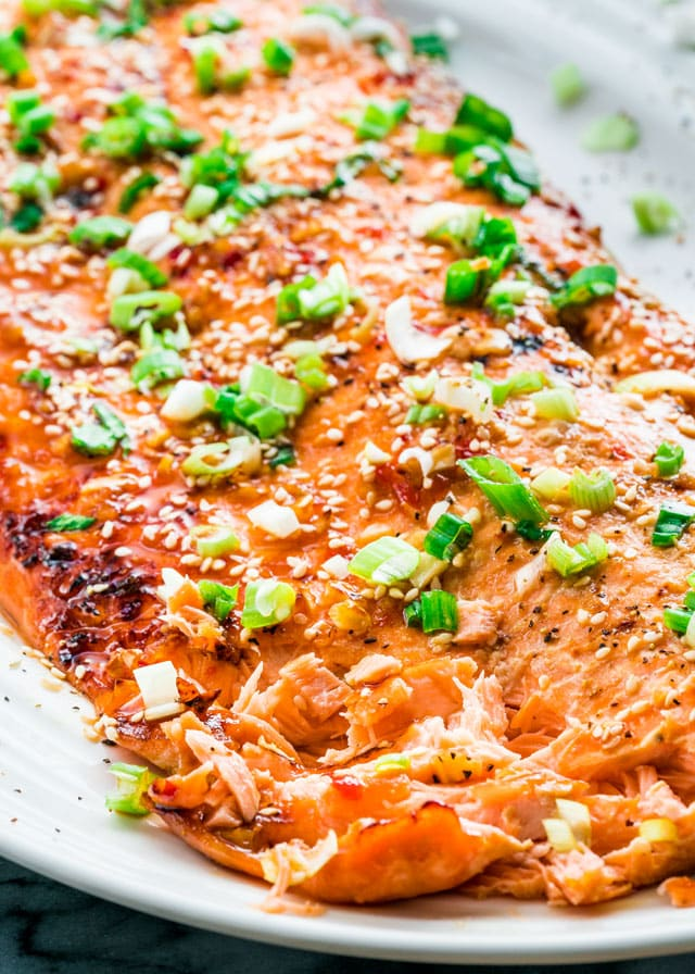 glazed salmon on a platter topped with sesame seeds and green onion