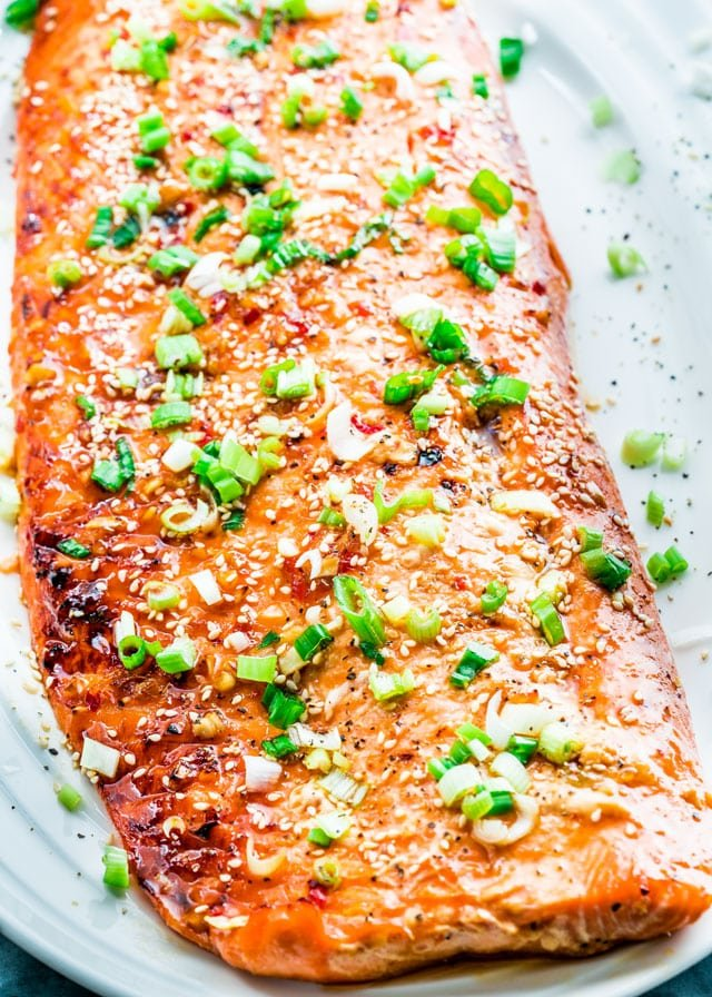 overhead of glazed salmon on a platter with sesame seeds and green onion
