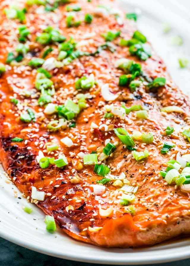 closeup of glazed salmon on a platter with sesame seeds and green onion