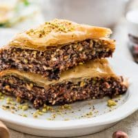 side view close up shot of two pieces of chocolate baklava stacked on a plate