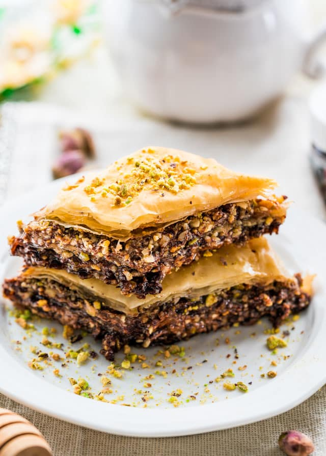 2 pieces of chocolate baklava stacked on a plate sprinkled with crushed pistachios